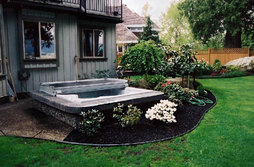 backyard spa surrounded by flowers