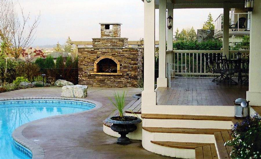 covered seating area around a pool with a fireplace